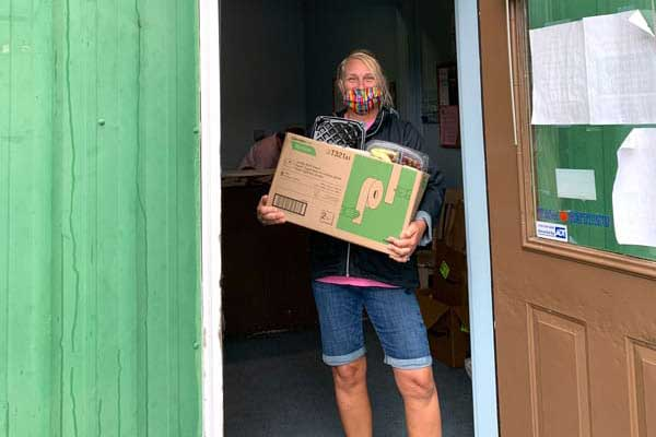 woman with box doorway food bank volunteer